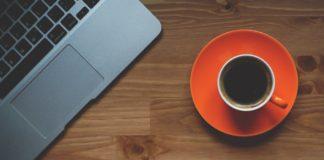 tazzina arancione di caffè con accanto un macbook aperto